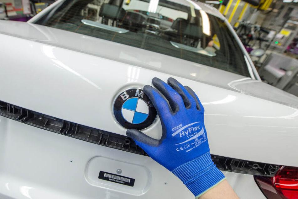 Ein Mitarbeiter montiert im BMW-Werk in Dingolfing (Bayern) ein BMW-Emblem auf den Kofferraumdeckel eines Fahrzeugs der 7er Reihe. (Archivbild)