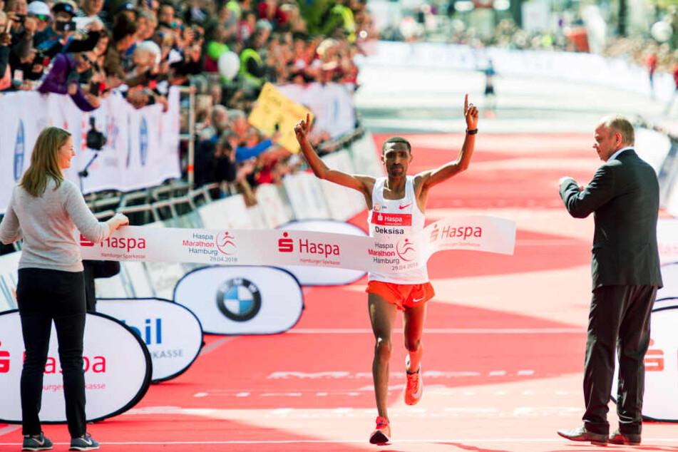 Solomon Deksisa aus Äthiopien jubelt beim Zieleinlauf des 33. Hamburg Marathon vor den Messehallen.