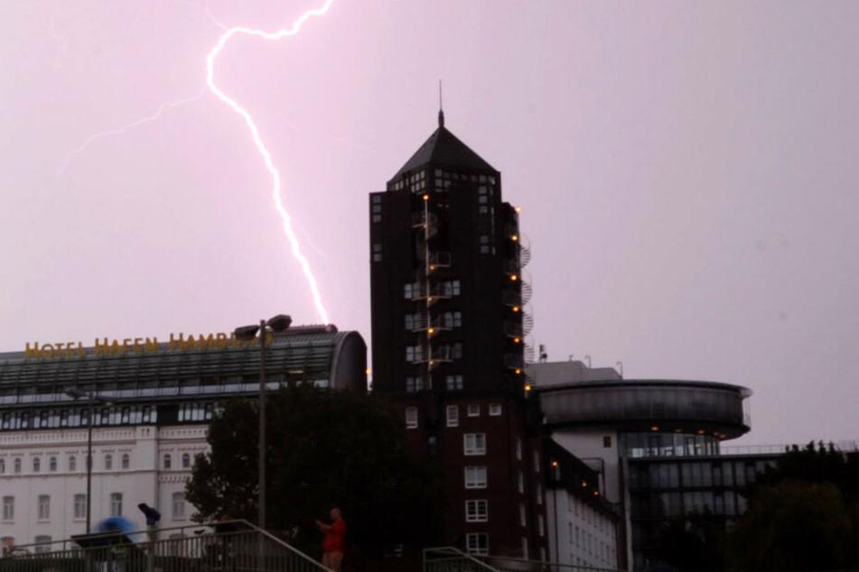 Ein Blitz zuckt bei den Landungsbrücken über den Hamburger Himmel. (Archivbild)