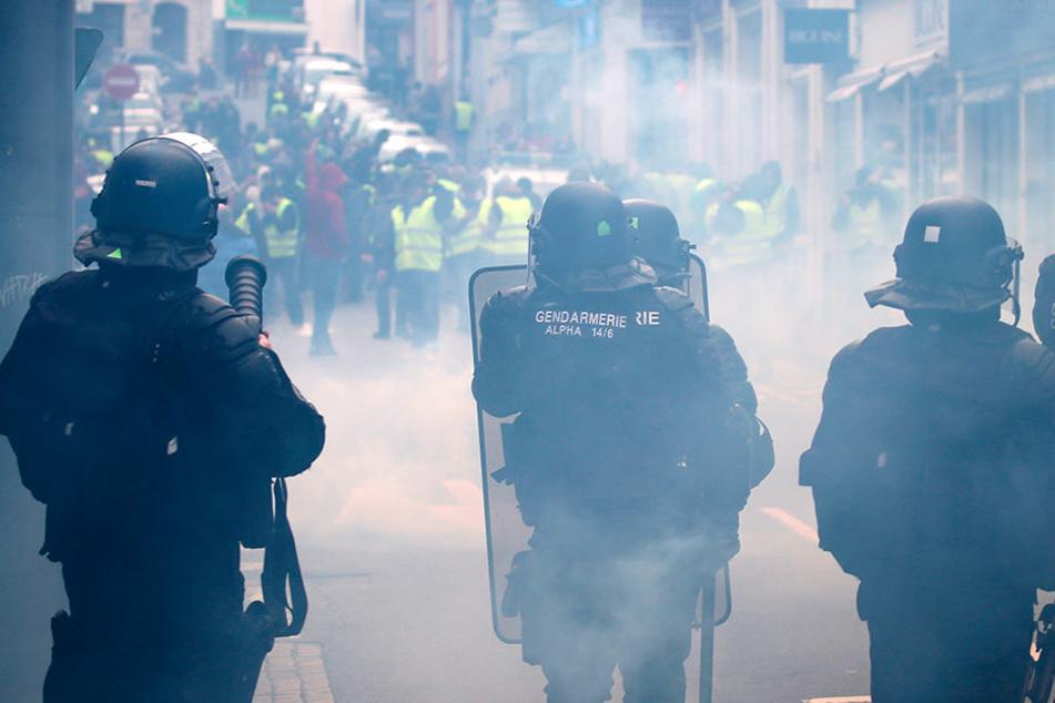 Gelbwesten-Demonstranten stehen am 18.12.2018 Bereitschaftspolizisten gegenüber.