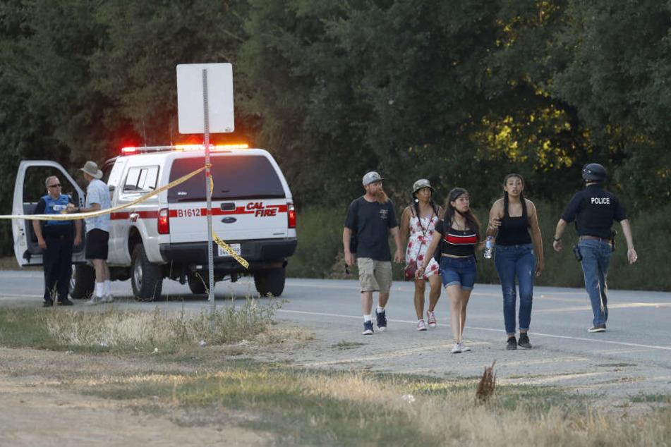 Menschen verlassen das Volksfest, nachdem drei Menschen durch Schüsse getötet wurden.