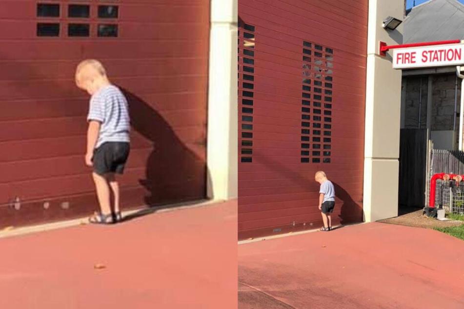 Der kleine Jozeph lehnt traurig mit dem Kopf gegen das Rolltor einer Feuerwehr.