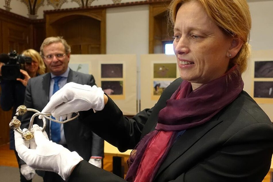 Karin Prien zeigt im archäologischen Landesamt in Schleswig-Holstein eine Ringfibel.