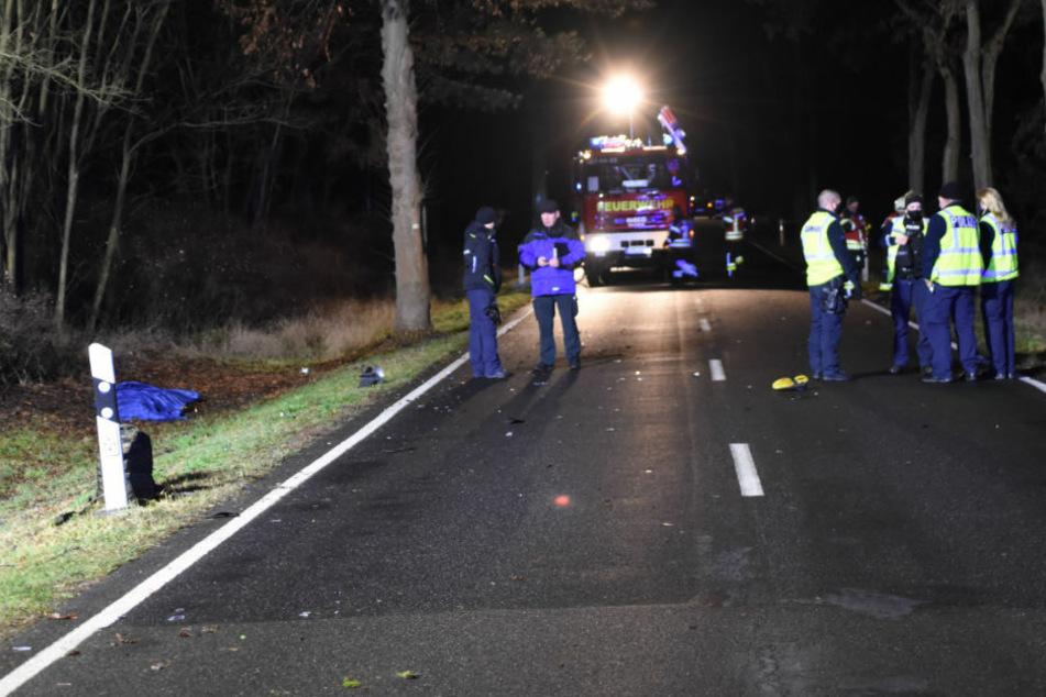 Einsatzkräfte stehen am Unfallort auf der Landstraße 741. Ein Schuh liegt mitten auf der Straße. Im Straßengraben auf der linken Seite liegt die Leiche des Unfallopfers, die mit einer blauen Abdeckplane verhüllt ist.