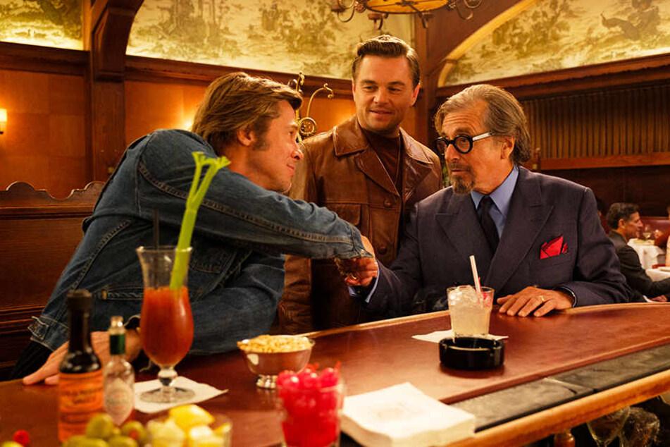 Rick Dalton (M., Leonardo DiCaprio) und sein Stuntman Cliff Booth (l., Brad Pitt) treffen sich mit dem Filmproduzenten Marvin Schwarsz (Al Pacino).