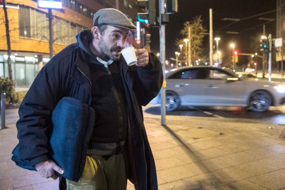 Ein Obdachloser geht mit einer neuen Wolldecke und einem Tee über die Straße.
