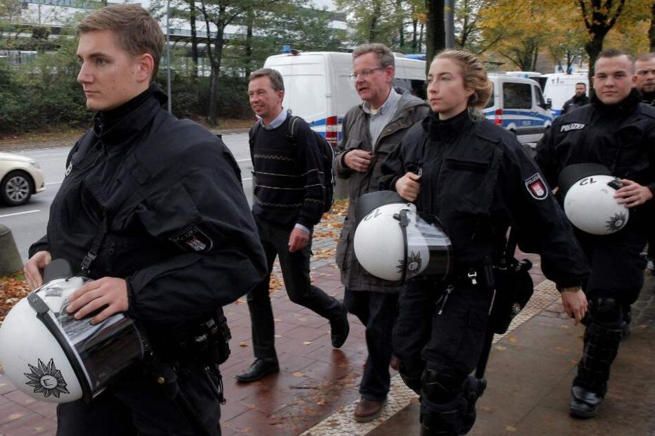 Von Polizisten geschützt verlässt Bernd Lucke den Campus.