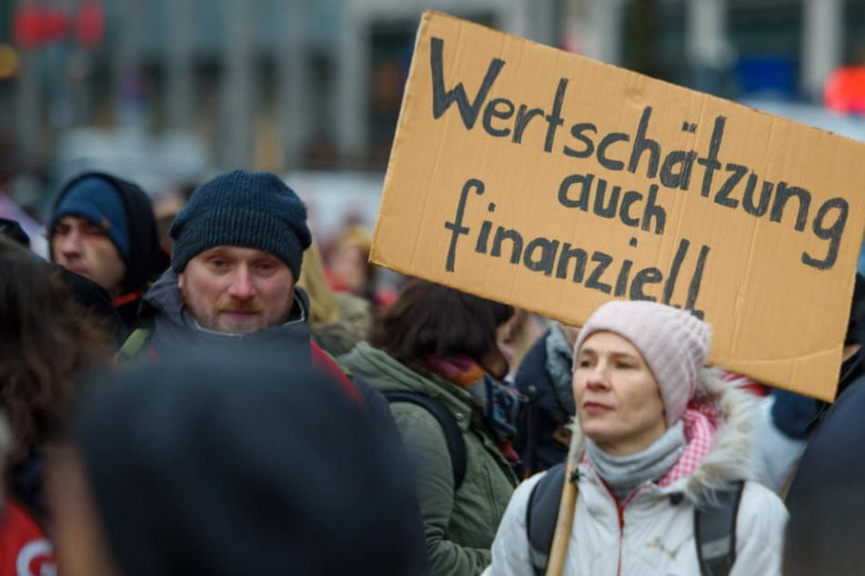 """ErzieherInnen und LehrerInnen stehen während eines Warnstreiks mit einem Schild """"Wertschätzung auch finanziell"""" auf dem Dorothee-Schlegel-Platz, um für faire Löhne und bessere Arbeitsbedingungen zu demonstrieren."""