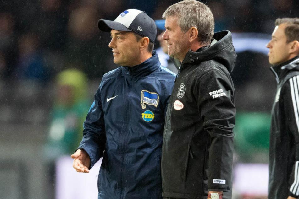Düsseldorfs Trainer Friedhelm Funkel (M.) und Herthas Trainer Ante Covic (l.) beobachten den Schiedsrichter vor der Elfmeter-Entscheidung für Düsseldorf.
