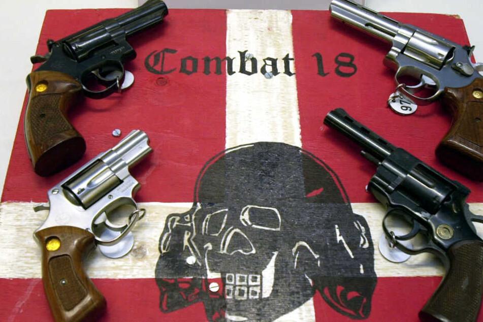 """Das Archivbild zeigt Waffen und ein Schild der nun verbotenen Neonazi-Gruppe """"Combat 18""""."""