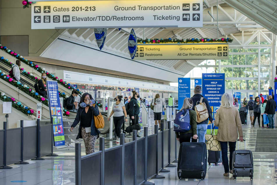 Travelers make their way through the Ontario International Airport in California as the number of Covid-19 cases are on the rise.