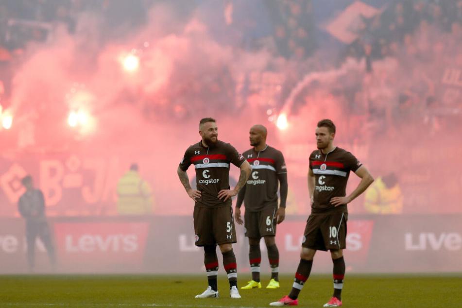 Im Millerntor Stadion (vlnr.): St. Paulis Marvin Knoll, Christopher Avevor und Christopher Buchtmann schauen nach einem Tor für den HSV recht bedrückt drein.