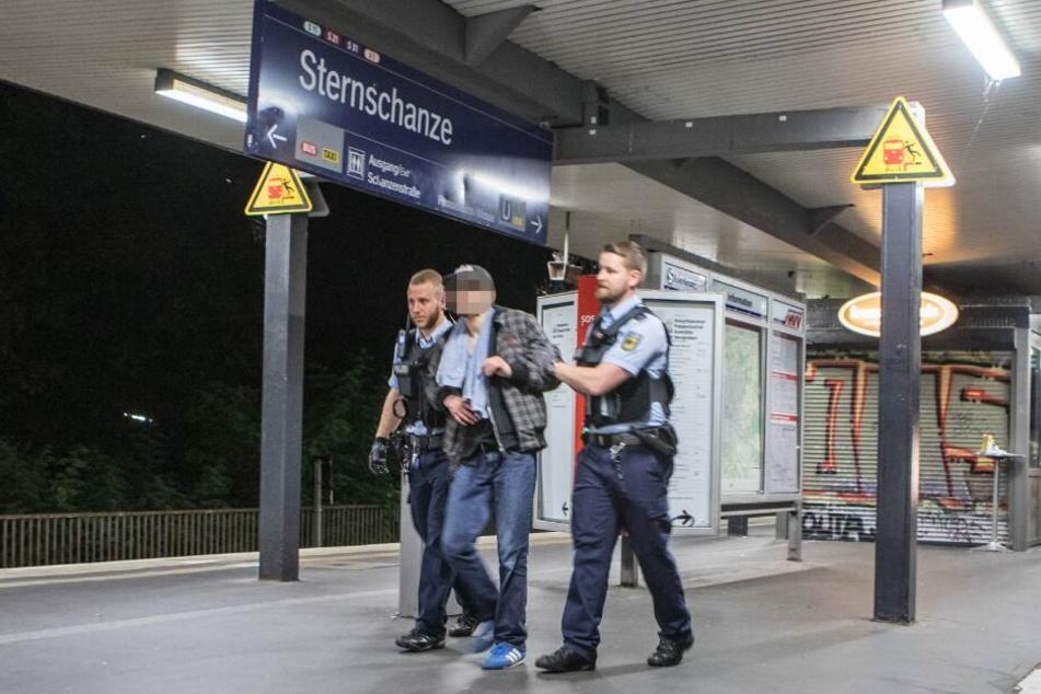 Zwei Beamte führen den betrunkenen Mann ab.