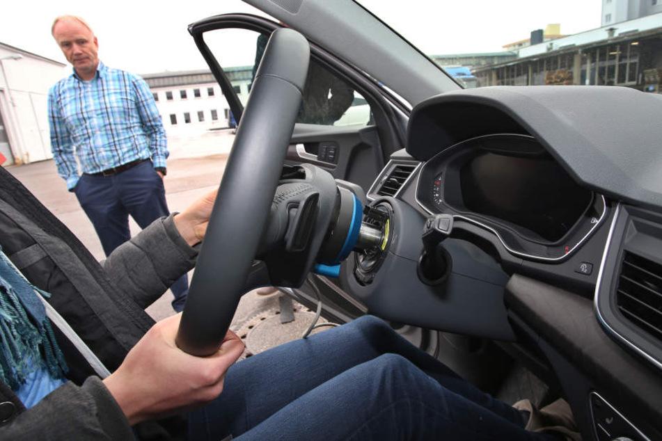 Bernhard Schick vom Forschungsbereich Fahrerassistenzsysteme der Hochschule Kempten steht an einem mit Messgeräten ausgsetatteten Auto.