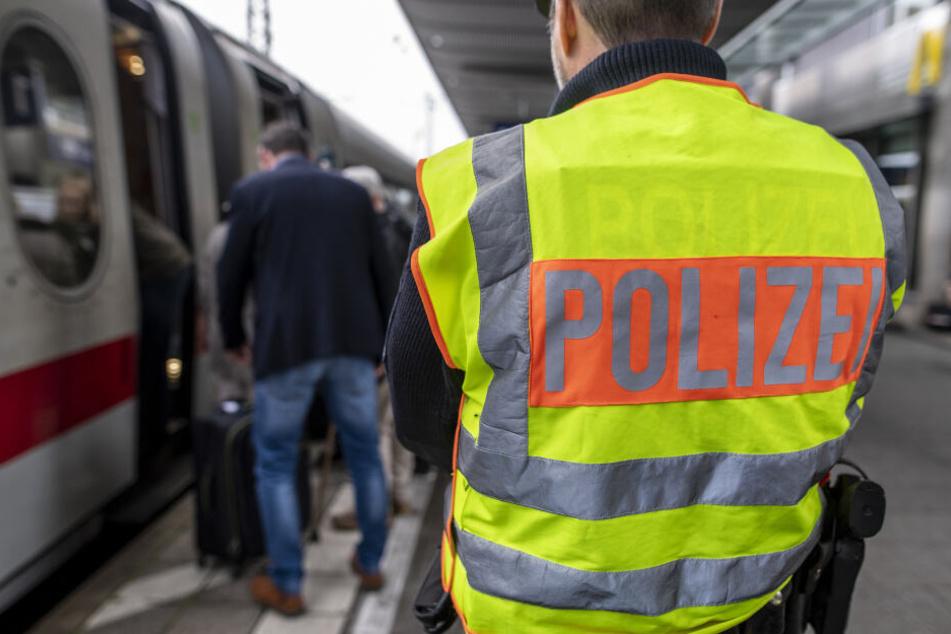 Ein Beamter der Bundespolizei beobachtet den Einstieg von Passagieren in einen Zug.