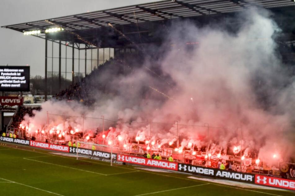 Fans des FC St. Pauli brennen Pyrotechnik ab während eine Anzeigetafel vor dem abbrennen von Pyrotechnik warnt.