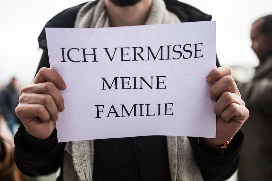 """Ein Mitglied des Flüchtlingsrats hält ein Schild mit der Aufschrift """"Ich vermisse meine Familie"""" in den Händen."""