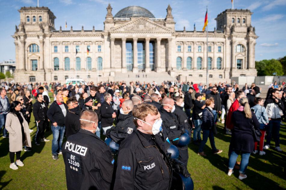 Polizeibeamte mit Mund-Nasen-Schutz stehen in einer Menschenmenge auf der Reichstagswiese vor dem Reichstagsgebäude.