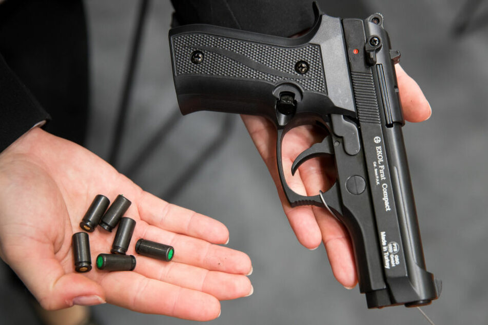 Ein Beamter hält eine Schreckschusswaffe mit Platzpatronen in der Hand. (Archivbild)