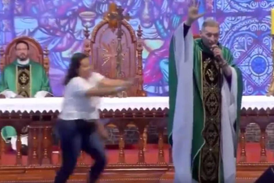 Hier sieht man die Frau, wie sie auf den Priester zu läuft.