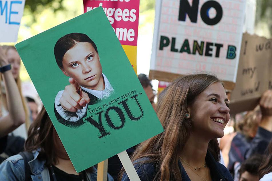 """Zahlreiche Menschen hören bei einer Demonstration den Sprechern des """"UK Student Climate Network"""" zu und marschieren mit Protestplakaten."""