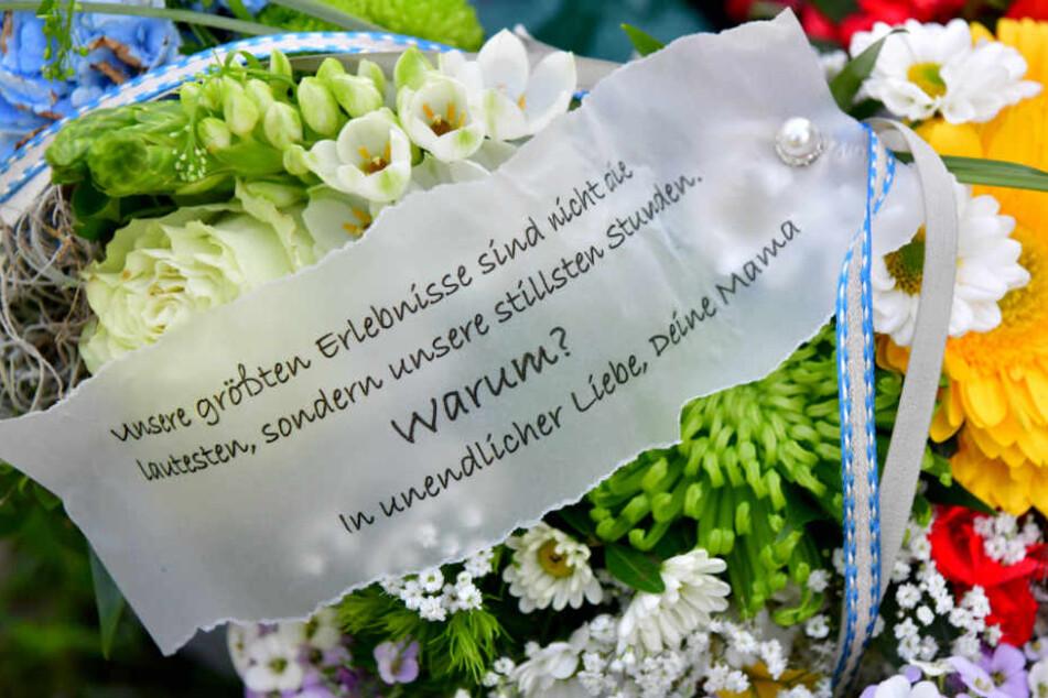 Ein Spruchband auf einem Blumengebinde von der Mutter des Opfers liegt bei der Trauerfeier am Grab des Jungen.