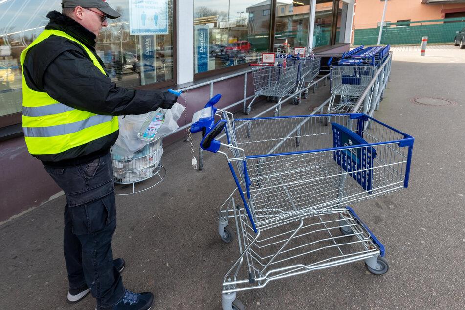 Bei Aldi an der Zwickauer Straße desinfiziert ein Security-Mitarbeiter jeden Einkaufswagen.
