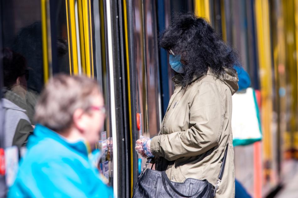 Eine Frau steigt in Schwerin mit Schutzmaske und Handschuhen in eine Straßenbahn ein. (Archivbild)