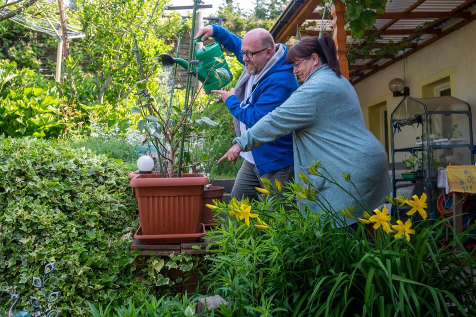 """Kathrin (50) zeigt """"Poschi"""" im Garten ganz genau, wo er gießen darf."""