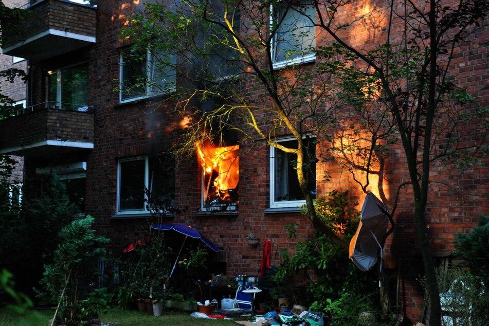 Die Flammen schlagen aus dem Fenster gegen das Mehrfamilienhaus.