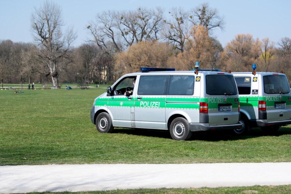 Zwei Polizeifahrzeuge stehen im Englischen Garten. Aufgrund der aktuellen Corona-Krise gelten in Bayern ab morgen weitreichende Ausgangsbeschränkungen.