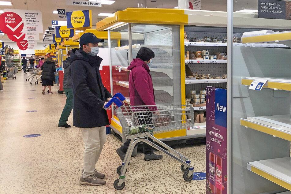 Ein Mann geht mit Maske durch einen Tesco-Supermarkt.