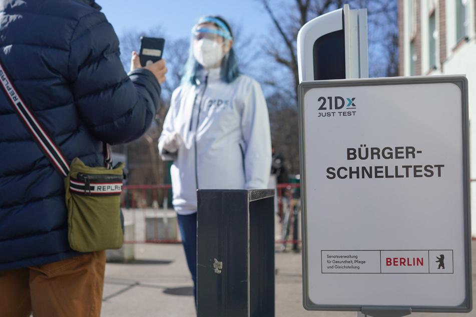Eine Mitarbeiterin der Betreiber-Firma 21Dx GmbH und ein Bürger stehen vor einem Corona-Schnelltestzentrum in der Lehrter Straße. Seit Montag ermöglicht die Bundesregierung allen Bundesbürgern kostenfreie Corona-Tests.