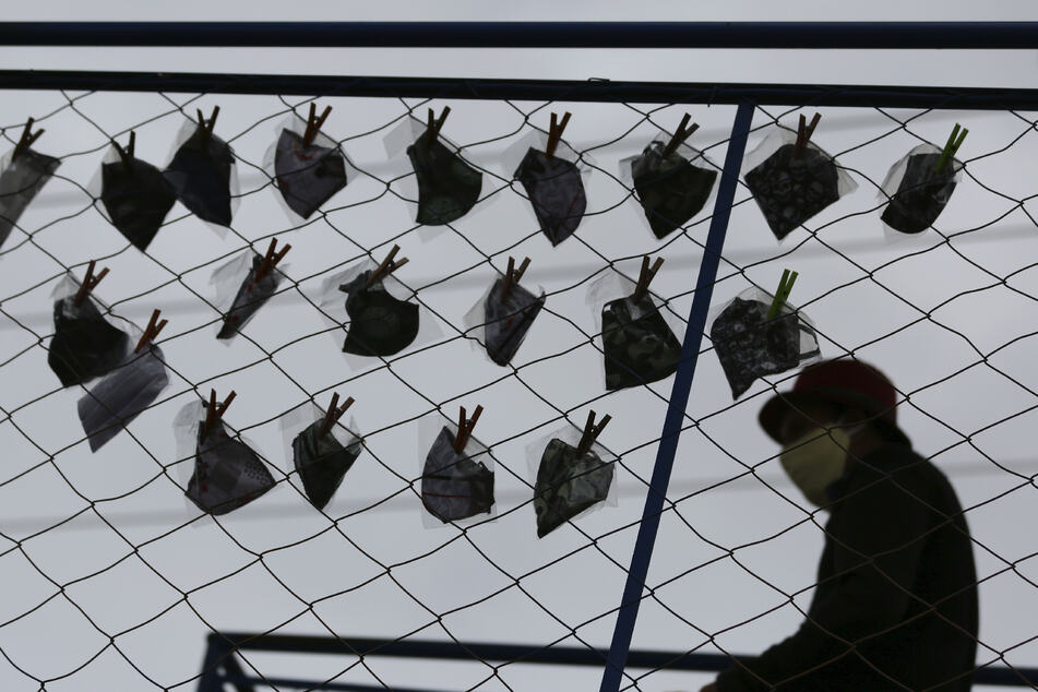 Ein Verkäufer sitzt inmitten der Corona-Pandemie in Brasilien neben Mundschutzmasken, die er zur Schau an einem Gitter angehängt hat.