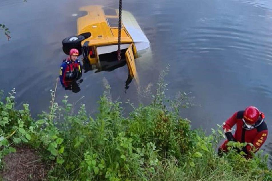 DLRG-Taucher befinden sich im Wasser bei dem Campingbus, an dem ein Seil befestigt ist.