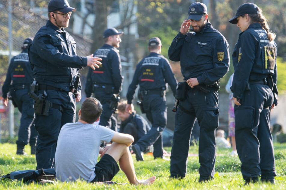 Stuttgart, 19. März: Polizisten sprechen mit einem jungen Mann in einer Parkanlage.