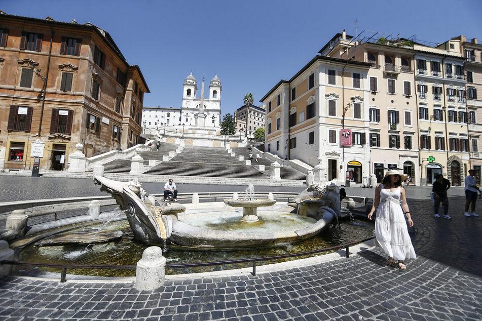 """Rom: Einzelne Touristen stehen am Brunnen """"Fontana della Barcaccia"""" vor der Spanischen Treppe, einem der Touristen-Hotspots. Die Zahl der ausländischen Touristen in Italiens Hauptstadt ist wegen der Corona-Pandemie extrem niedrig."""