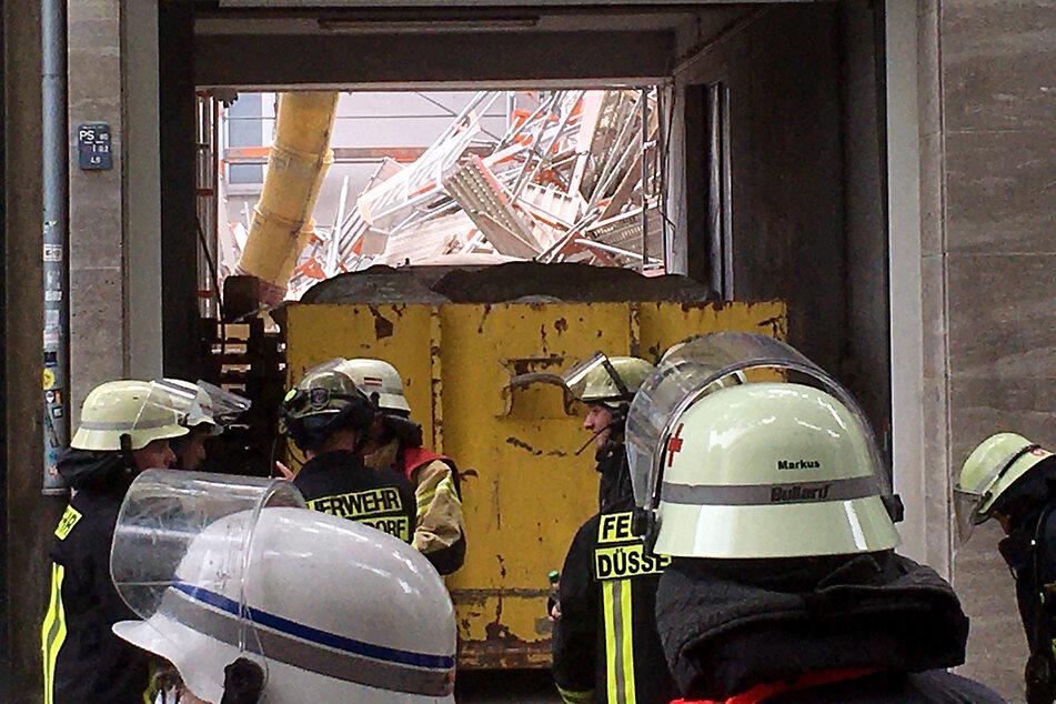Einsatzkräfte der Feuerwehr stehen vor einer Hauseinfahrt, durch die ein eingestürztes Gerüst zu sehen ist.