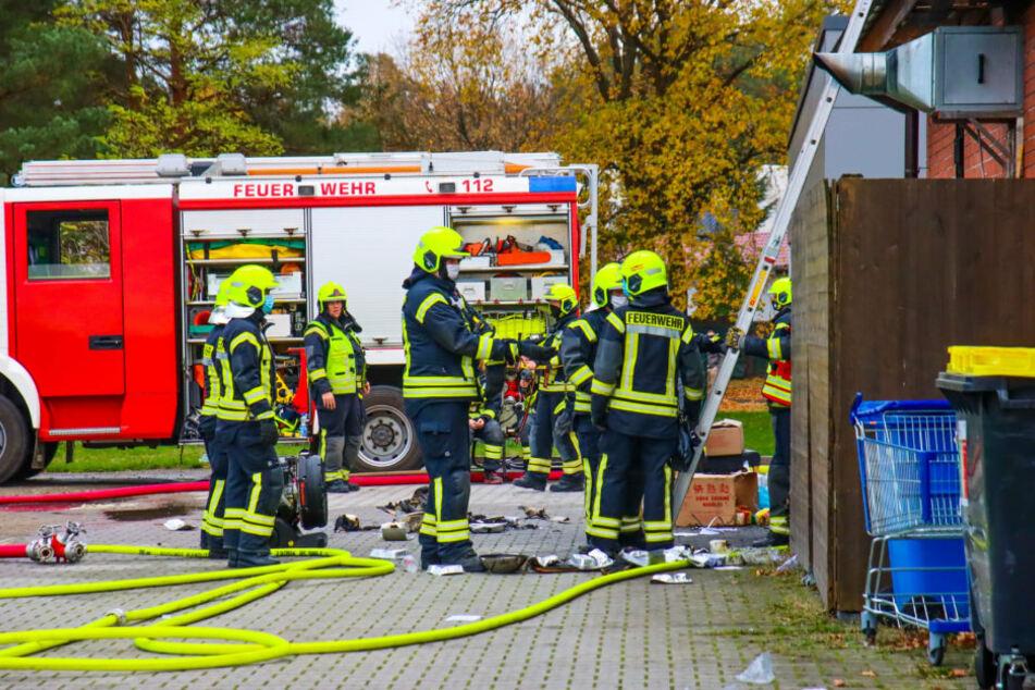 Einsatzkräfte der Feuerwehr stehen vor dem Imbiss in Wandlitz (Barnim).
