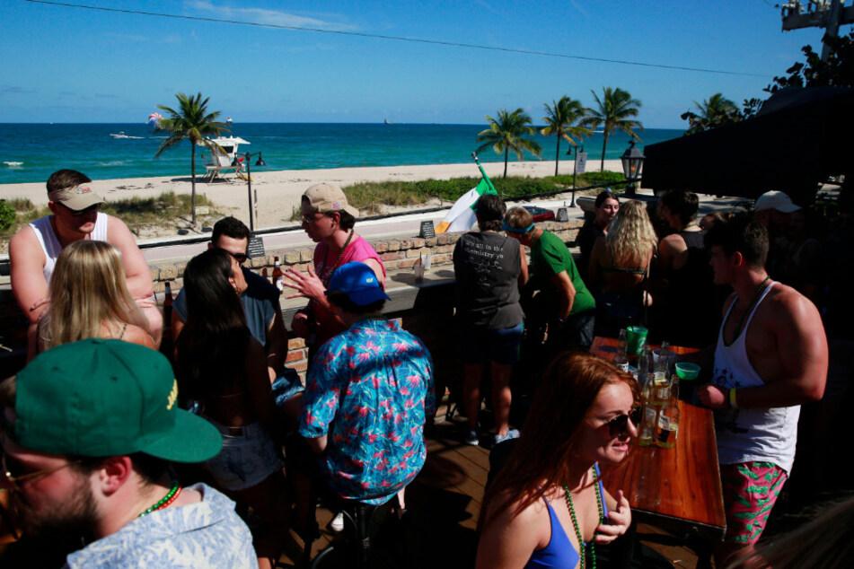 """Studenten, sogenannte """"Spring Breakers"""", stehen auf einer Terrasse an einem Strand zusammen."""