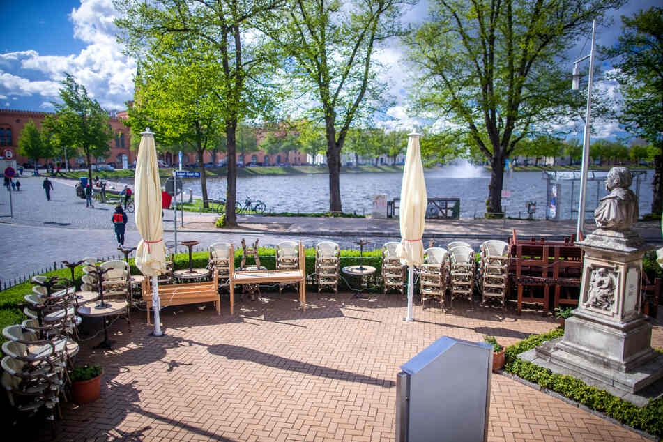 Noch stehen die Stühle von einem Restaurant gestapelt auf der Terrasse.