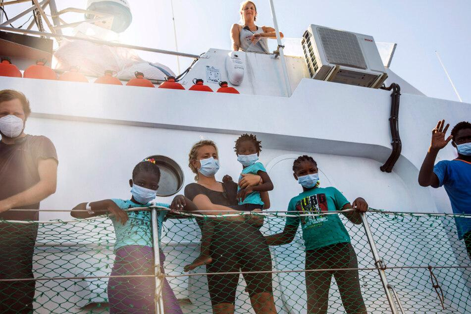 """Mitglieder der Besatzung und gerettete Menschen stehen an Bord der """"Louise Michel"""", das vom renommierten Künstler Banksy finanziert wird."""