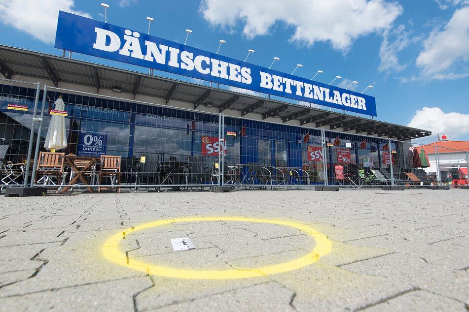 Eine Spur ist nach dem Überfall auf einen Geldtransporter auf dem Parkplatz vor einer Filiale des Dänischen Bettenlagers in Cremlingen markiert. (Archivbild)