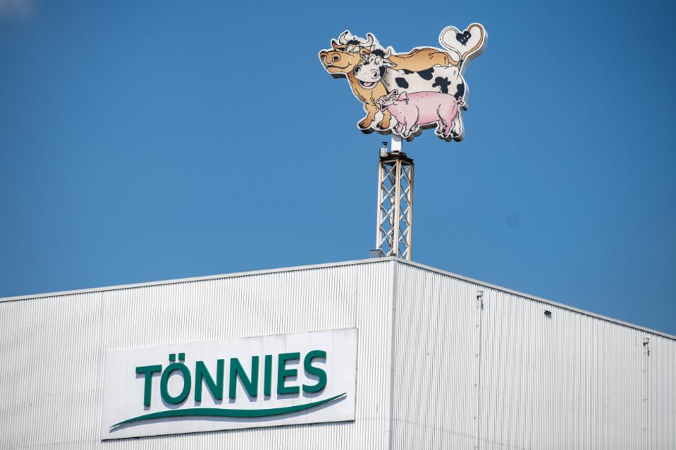 Auf dem Dach eines Gebäudes auf dem Werksgelände steht das Logo der Firma Tönnies in Form von zwei Kühen und einem Schwein.