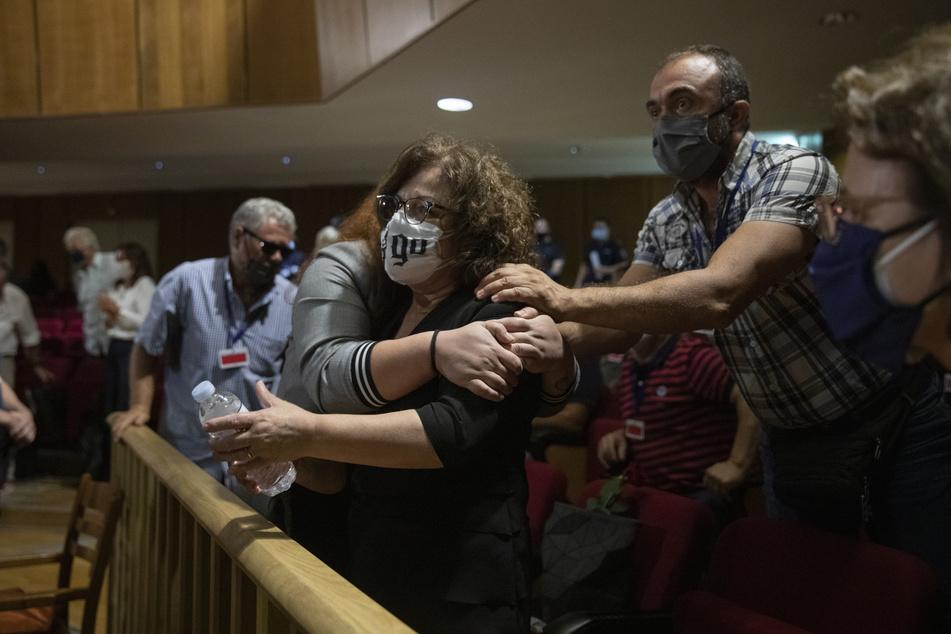 Magda Fyssa, Mitte, die Mutter des verstorbenen griechischen Rap-Sängers Pavlos Fyssas, der 2013 von einem Anhänger der rechtsextremen Golden Dawn-Partei erstochen und getötet wurde, was zu einer Razzia gegen die Partei führte, feiert unmittelbar nach der Verkündung des Urteils eines Gerichts.