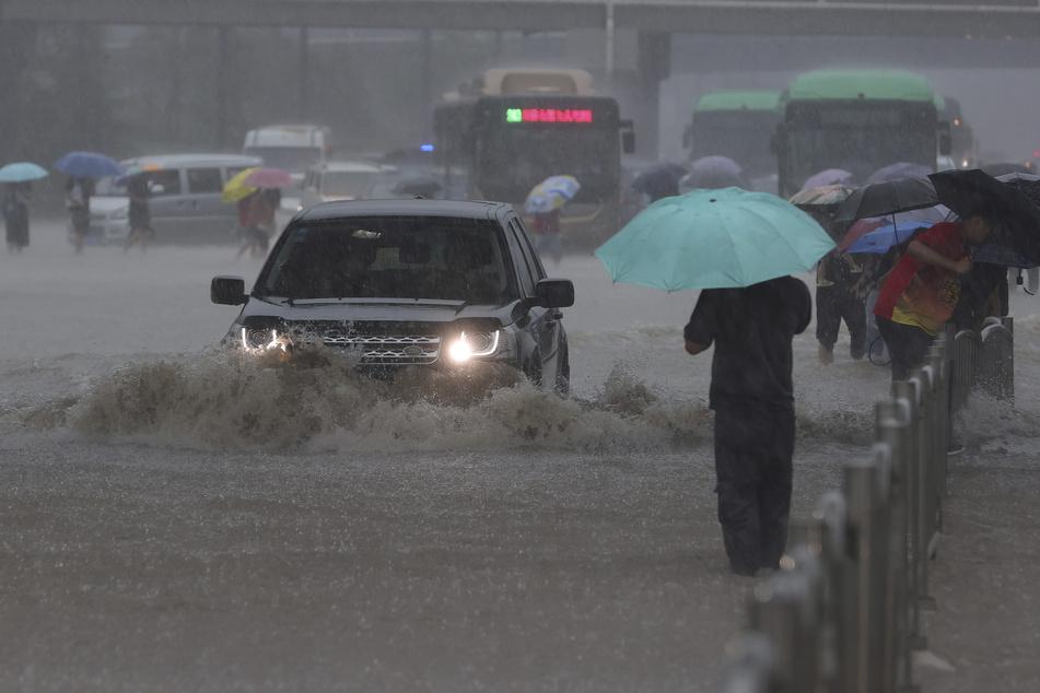 Ein Auto fährt in der zentralchinesischen Provinz Henan über eine überflutete Straße.