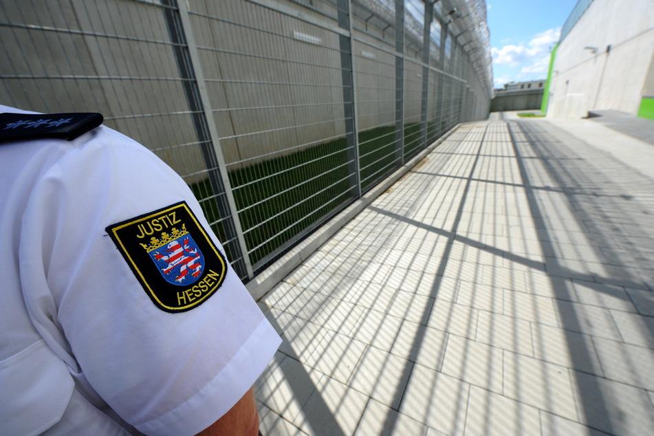 Ein Justizbeamter steht an den Sicherheitszäunen der Justizvollzugsanstalt Frankfurt/Main.