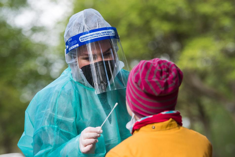 Eine medizinische Mitarbeiterin führt bei einem Mädchen einen Corona-Test durch.