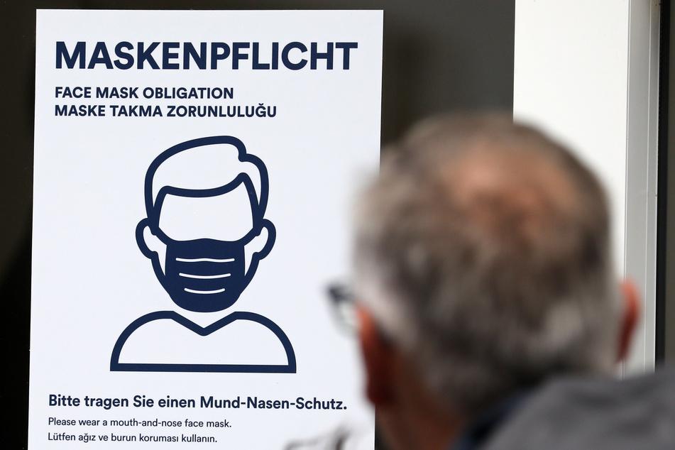 """Auf einem Aushang steht in mehreren Sprachen """"Maskenpflicht Bitte tragen Sie einen Mund-Nasen-Schutz"""", ein Mann geht daran vorbei."""