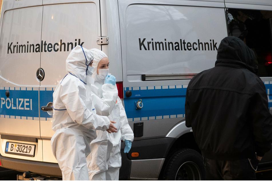 Kriminaltechnikerinnen stehen an einem Einsatzfahrzeug vor einem Wohnhaus in der Mahlower Straße in Berlin-Neukölln.